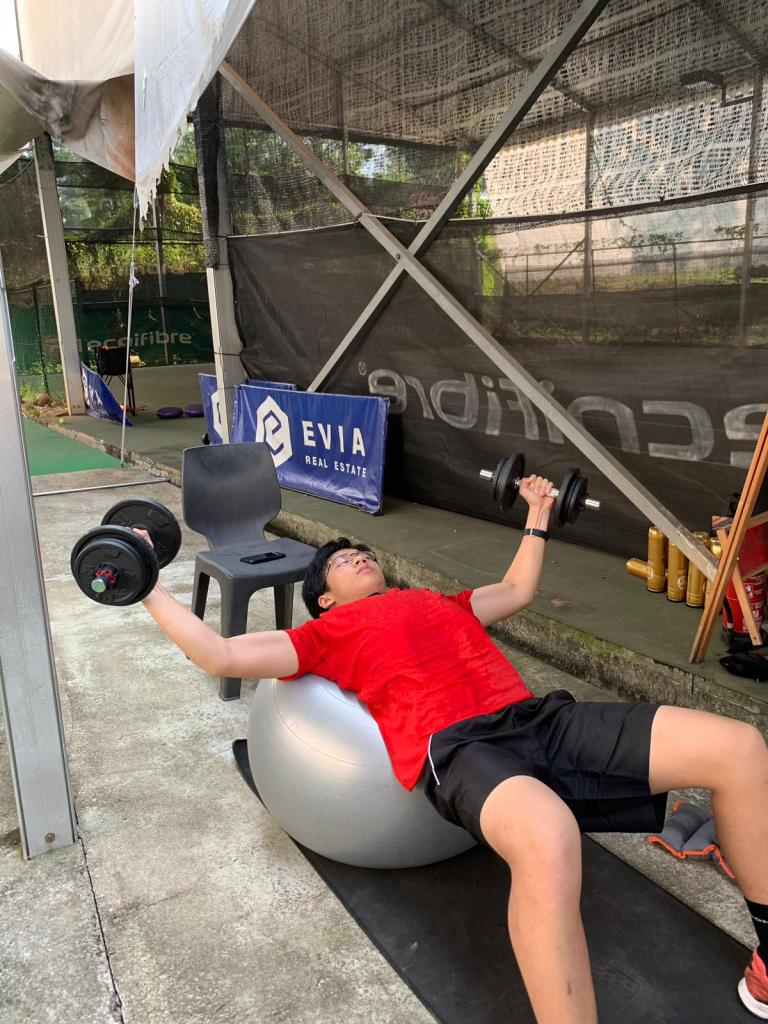 Aaron Chiu does single dumbbell flyes for physical conditioning