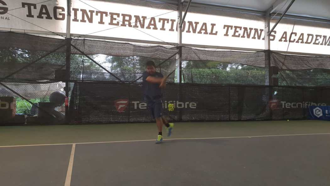 Coach Rapeepat Thonghatta has a long follow through on his backhand