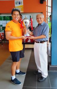 Coach X with orange Sergio Tacchini top winning a tennis trophy
