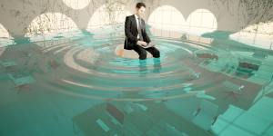 Business man with a computer is sitting on a floaty in under water office