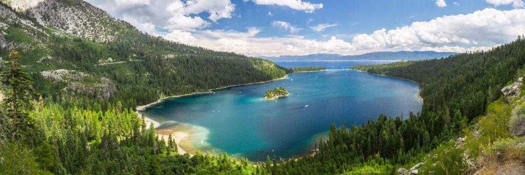 A wide photograph of Emerald Bay. The bay posses blue/green waters that are iconic. In the middle of the bay, sits a small island, Fanette Island.