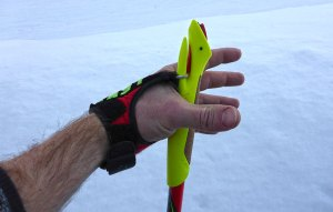Notice the white loop that's essentially lassoed around the stem on the backside of the cross-country ski pole handle. You slide the loop over that stem until the red wedge (down the slot) locks it into place. © Jared Manninen