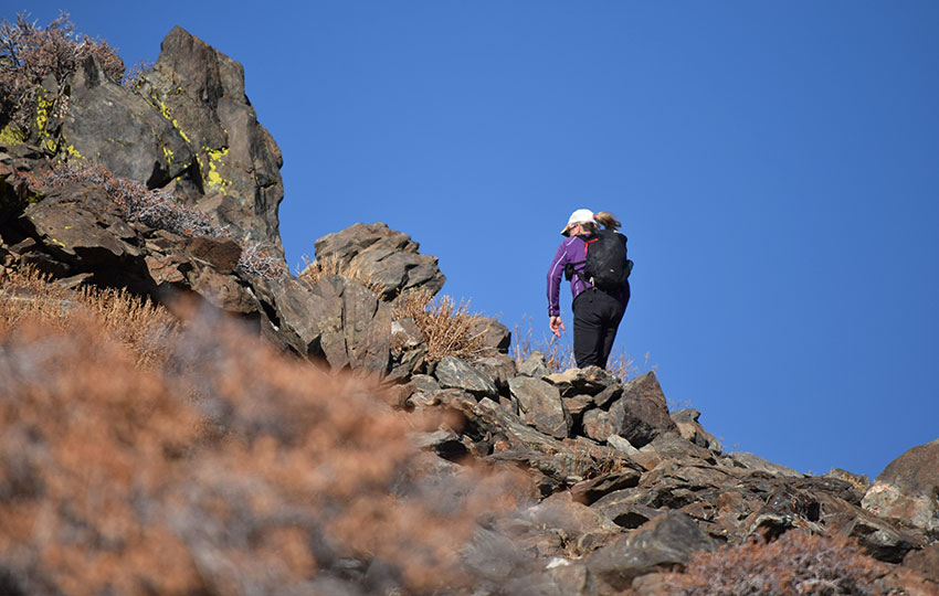 Hiker traveling up a rocky trail with blue skies above