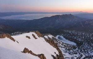 Snowy mountains and blue lake at sunrise