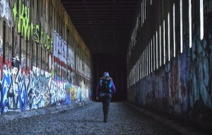 Hiker walking through old train tunnels with graffiti on the walls