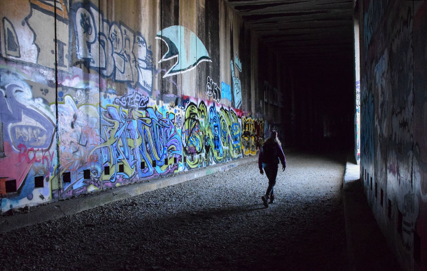 Hiker walking through old train tunnels lined with graffiti