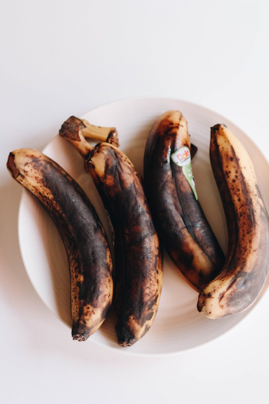 four ripe bananas on a white plate