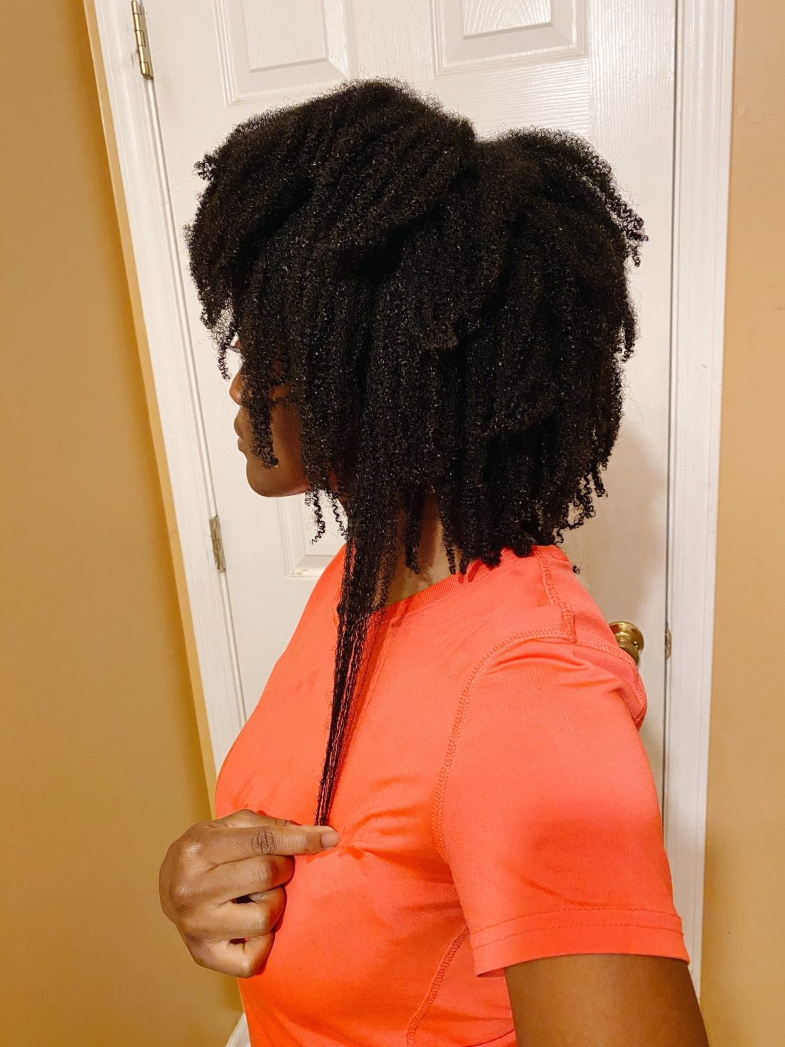 Woman with 4C natural hair that has been washed and conditioned
