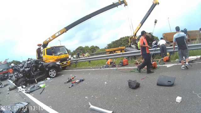 Workers are scene with cranes and other equipment at the scene of a traffic accident on a freeway in Taiwan