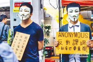 Two young men wearing guy fawkes masks support student protesters in Taiwan