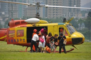 Women and children evacuees disembark from a helicopter in New Taipei City's Hsintien District after being airlifted from Wulai