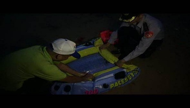 A man and a patrolman pack up an inflatable toy boat used to cross from China to Taiwan
