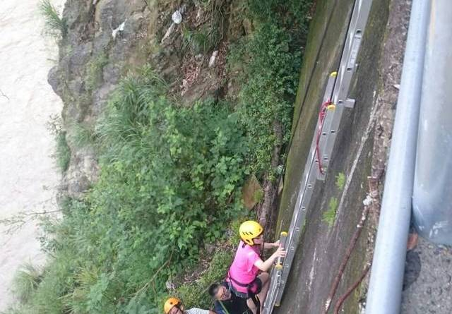 Tourists using a ladder to climb out of a flooded gorge in Wulai District, New Taipei City