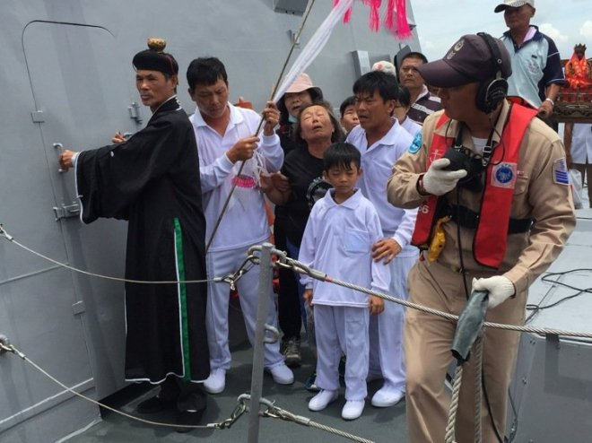 a daoist priest is seen with mourners on the deck of a navy vessel in Tainan, Taiwan