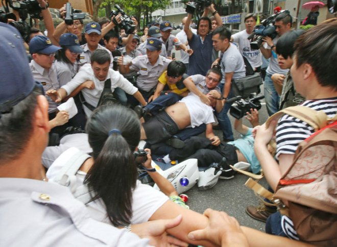 a police motorcycle is knocked over as police and protesters fight in Taipei