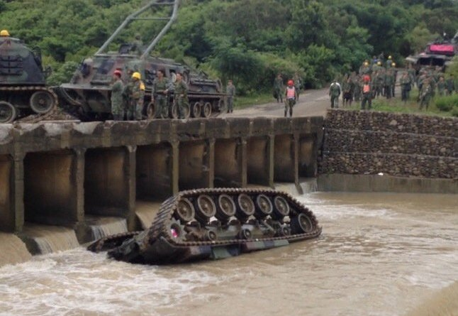 A CM11 Tank upside down in the water after falling off a bridge.