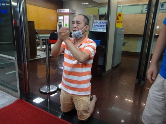 a man kneels in apology after being granted bail in a Taipei Distric Court