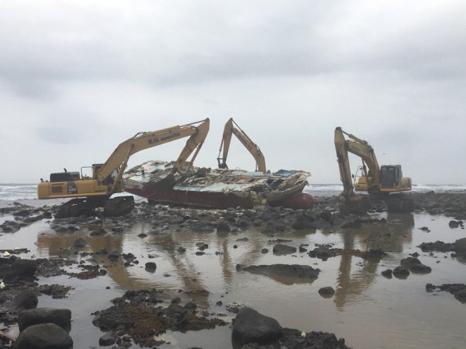 backhoes flip an overturned vessel up after it drifted aground on the coast of New Taipei City