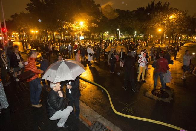 guest gathered in a park after being evacuated from Grand Formosa Regent Hotel, Taipei, February 25, 2017