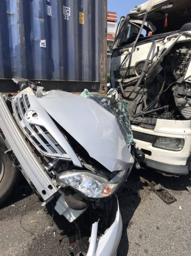 car crushed between two semi-trailers carrying shipping containers
