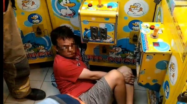 man with arm stuck in claw machine