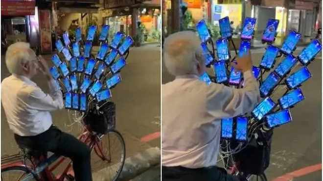 elderly Pokemon Go player with array of 30 phones mounted on handlebars of bicycle.