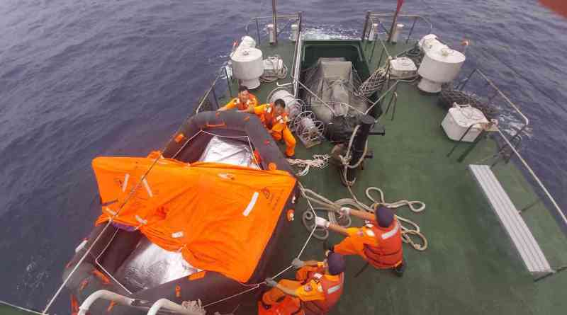 Taiwan Coast Guard officers retrieve an empty life raft after a ship sinks in the Taiwan Strait