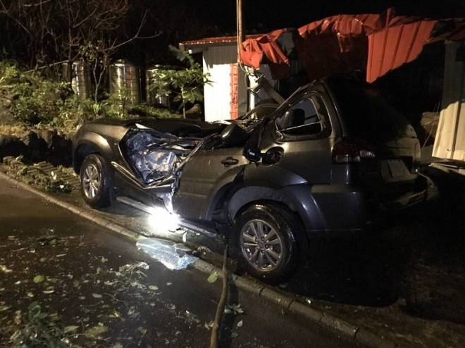 car flattened by boulder and damaged house