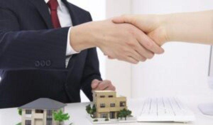 模型の家と握手する人