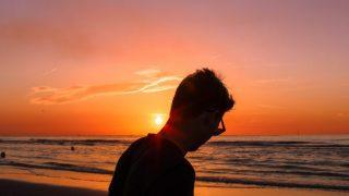 海岸で夕日をみる人