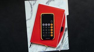 赤い手帳の上に置いてあるスマートフォン