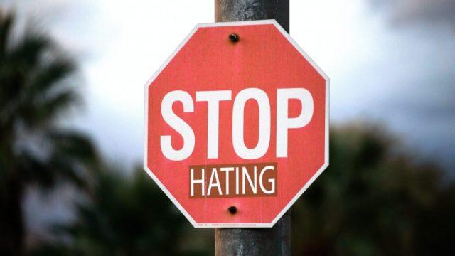 STOP HATINGと書かれた赤い看板