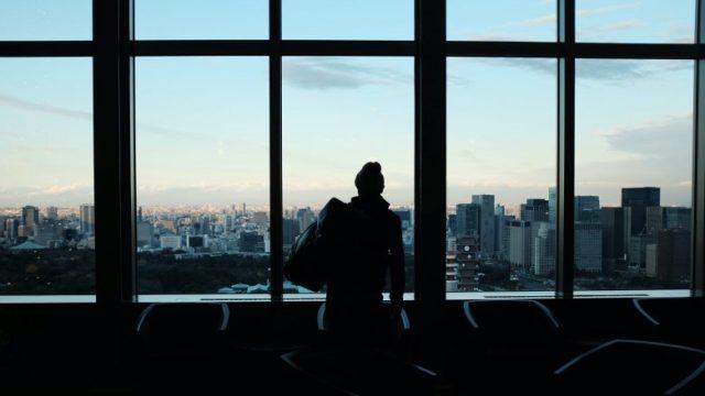 窓ガラスの外を見つめる人のシルエット