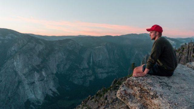 崖に座って景色を見る男性