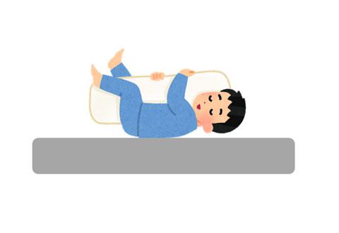 抱き枕を抱いて上向きに寝ている人