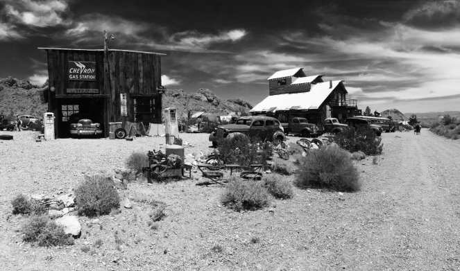 Black and white shot of Nevada ghost town Eldorado, a back roads attraction featuring old cars old buildings and desert scenery