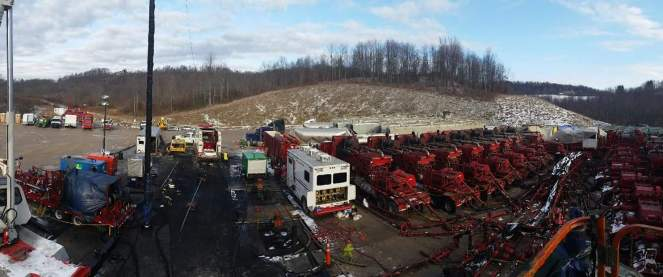 Shale oil fracking equipment and wireline trucks sit at the edge of a snowy forest
