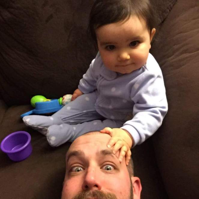 An adorable baby girl rests her hand on Daddy's head