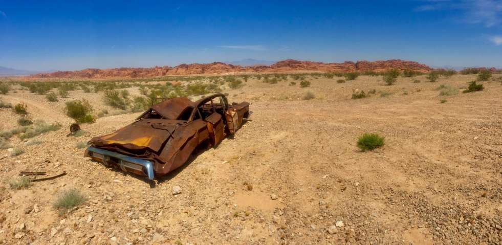 A rusty wrecked car sits in the desert in Red Rock Canyon State Park near Las Vegas