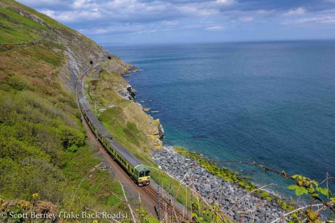 Ireland Cliff Walk from Bray to Greystones, with a DART train in the foreground by the Atlantic Ocean