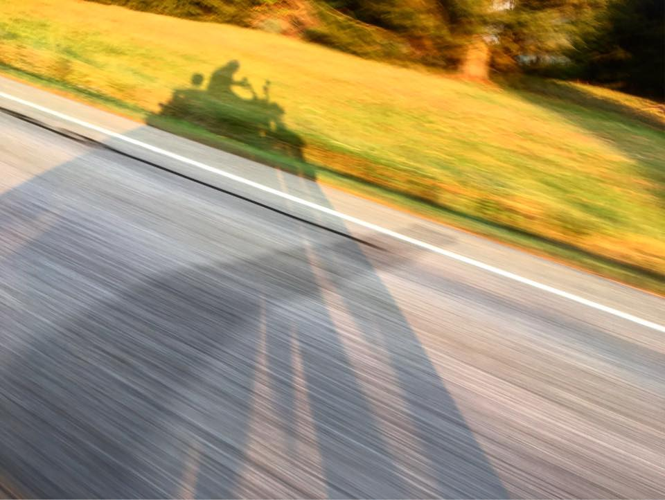 The silhouette of a Harley Davidson motorcycle and its rider races across the blurred country back road