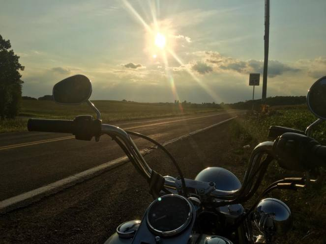 A blazing sun sets over a back road, all viewed between the handlebars of a Harley Davidson motorcycle