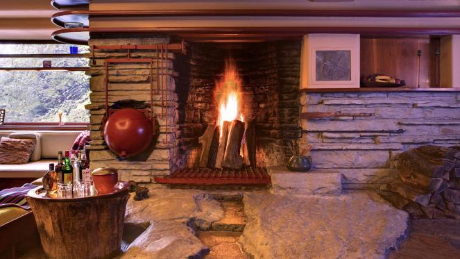 A rare interior shot inside the Frank Lloyd Wright designed Fallingwater house, capturing the massive Fallingwater Hearth and famous tea kettle ball and a blazing log fire