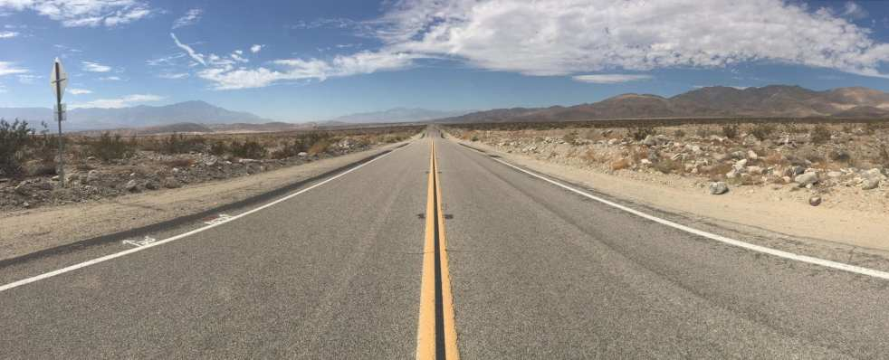 desert mountains road broad blue sky vanishing point