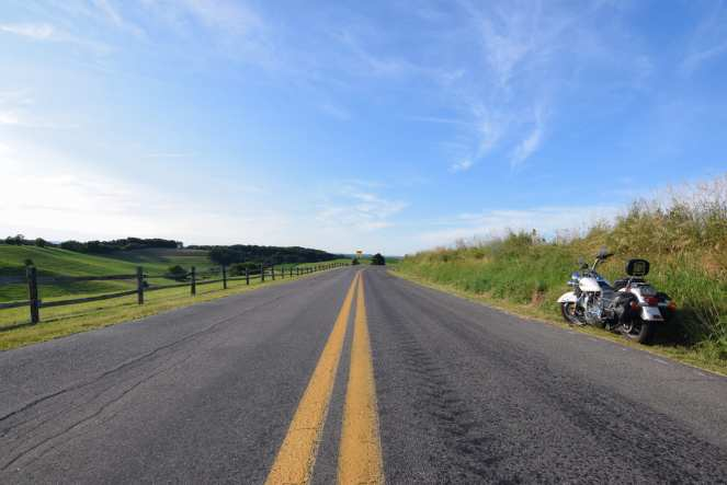 white harley davidson motorcycle broad back road tranquil countryside