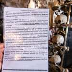 Sedlec ossuary bone church info card, back side, being held in front of a large display of human bones