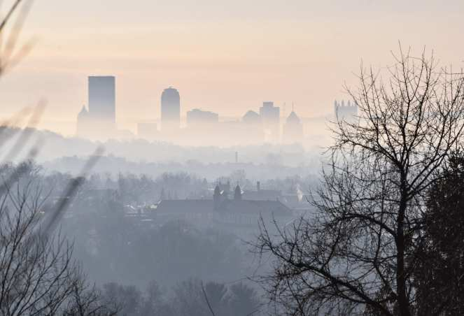 The sun rises on a hazy winter day, burning off the blanket of fog over the downtown skyline