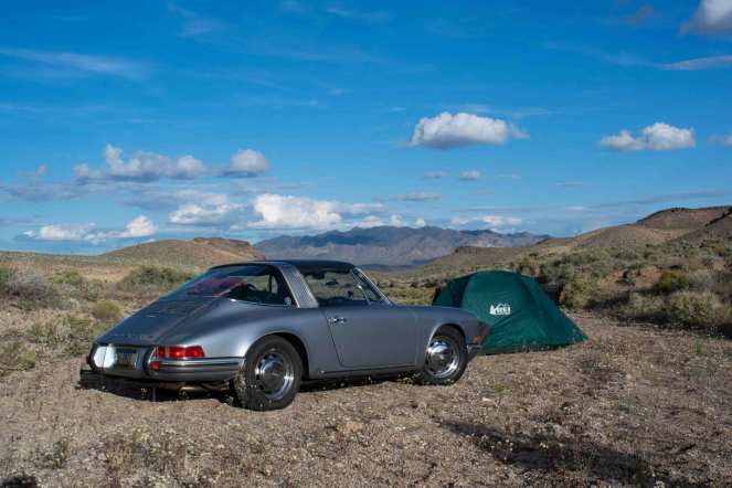 A silver 1969 Porsche 911 sits in front of a green tent in the desert of Nevada. Sharp mountains jab at the horizon.