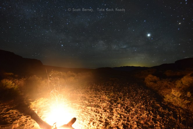 Our campfire lights up the desert floor while the Milky Way spans the dark night sky overhead.