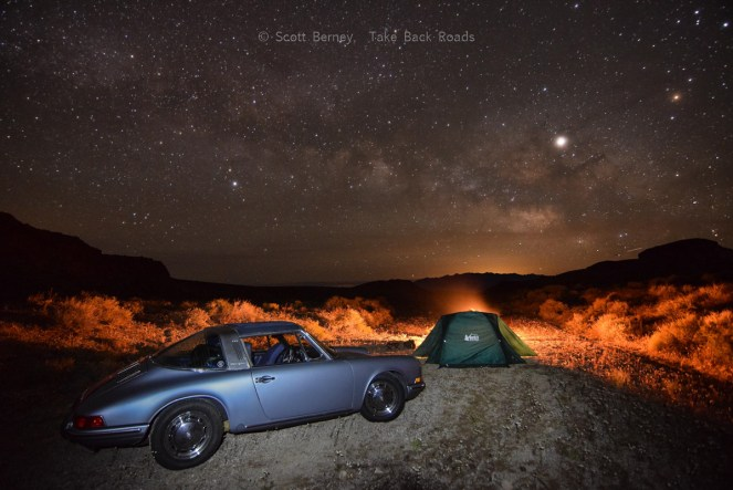 The Milky Way stretches across the night sky over a campfire, REI tent, and antique Porsche sitting in the Nevada desert